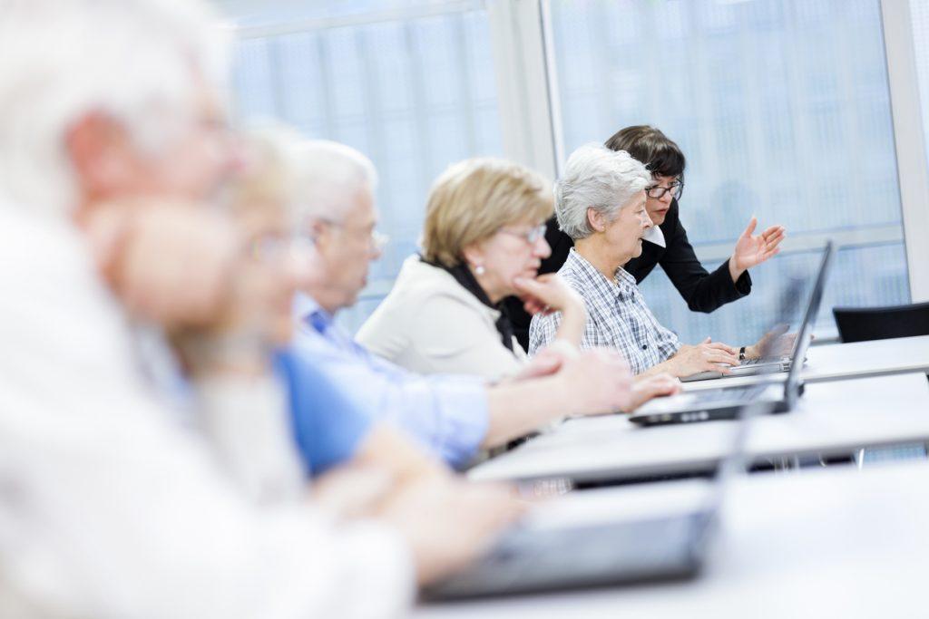 UI Design Best Practices for Seniors - Female Teacher Explaining New Computer Technology to Senior Woman