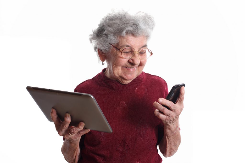 elderly woman holding tablet and smartphone - testing technology for seniors