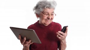 elderly woman holding tablet and smartphone - apps for older adults