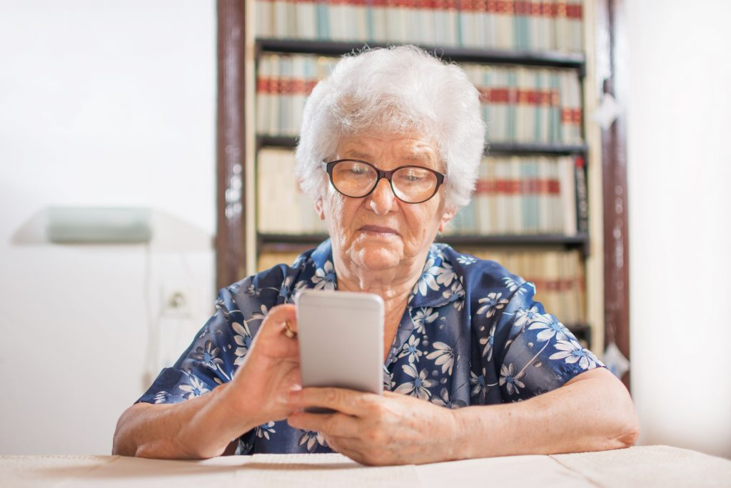 Vision Impairment Considerations in User Interface for Seniors - Elderly woman looking at a smart phone at home.