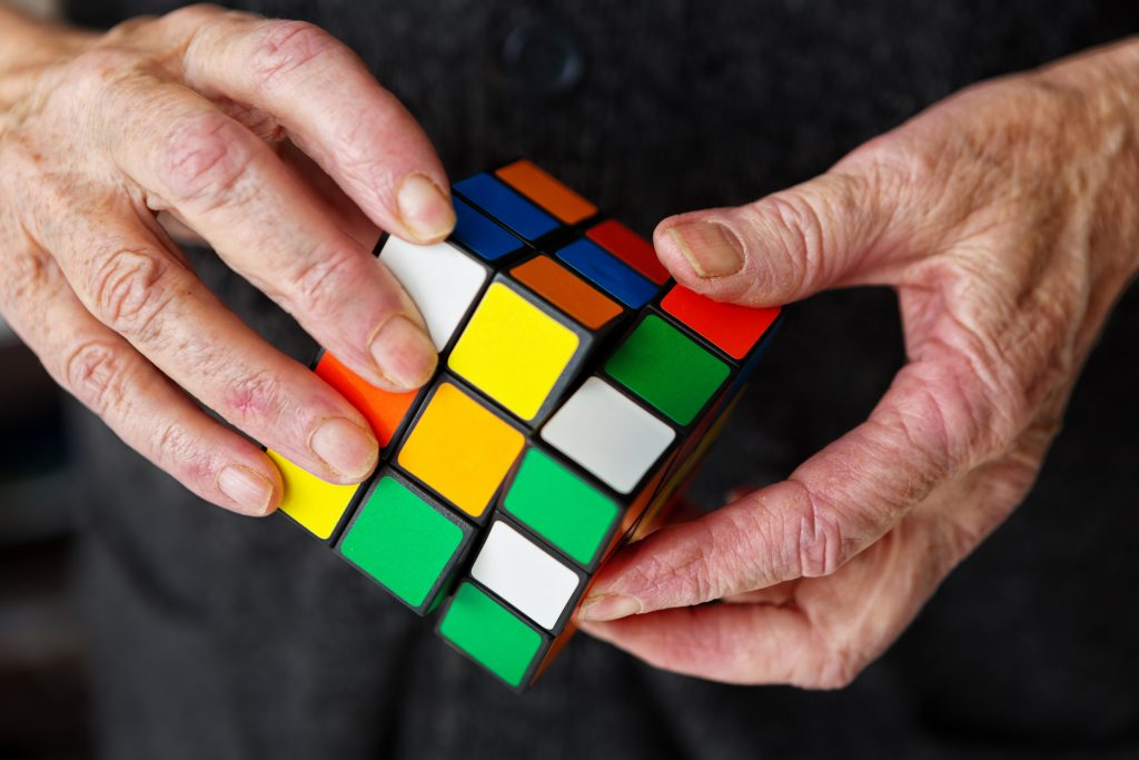 Hands holding multicolor cube - Designing technology for seniors