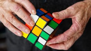 Hands holding multicolor cube
